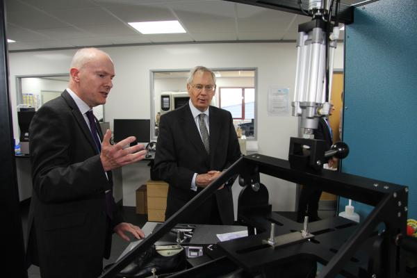 Technologist Mike George explains the SATRA slip rig to HRH The Duke of Gloucester
